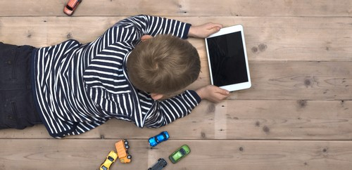 Modern generation. Kid using ipad on floor