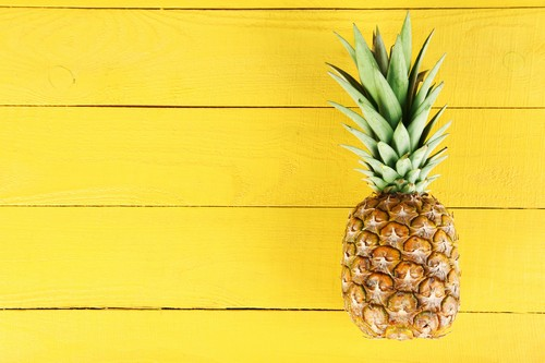 Ripe pineapple on a yellow wooden background
