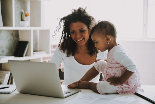 Young Smiling Freelancer with Daughter at Home. Working Freelancer. Young Businesswoman with Portable Device. Little Girl in Pink Dress. Window in Room. Baby with Mother. Woman in White Clothes.