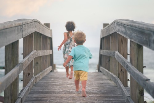 Toddler brother and his sister running on wooden deck on the beach, rear view
