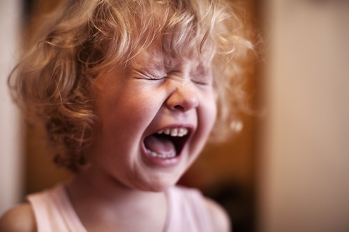 Crying little girl with curly hair closing her eyes.