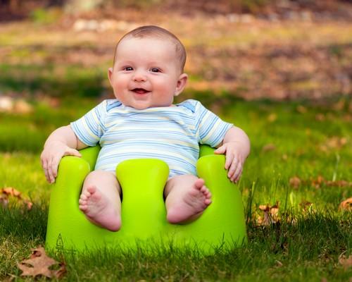 Happy infant baby boy using training seat