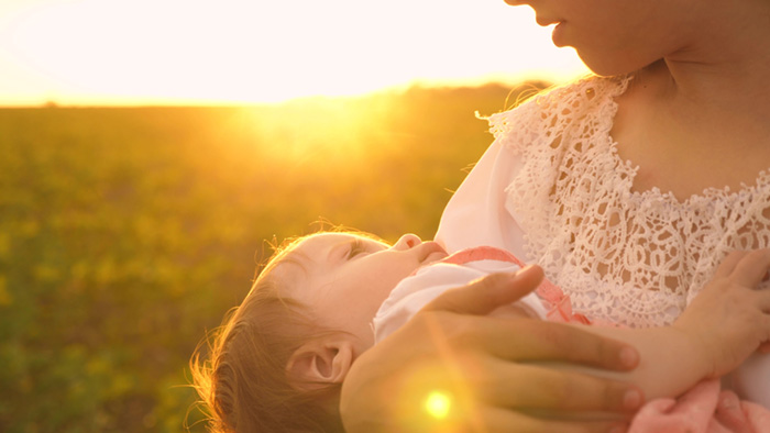 a little baby sleeps in arms of his mother, at sunset, slow-motion shooting