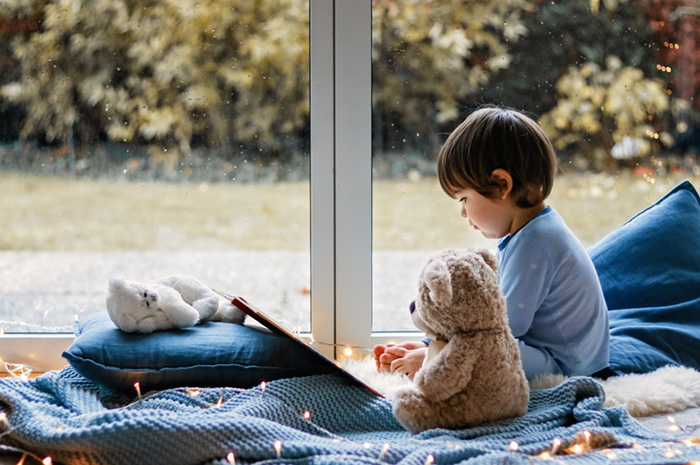 Cute little boy reading book with his teddy bear toy sitting cozy on pillows and knitted blanket near wet window with autumn garden at background. Cozy home. Winter holidays lifestyle.
