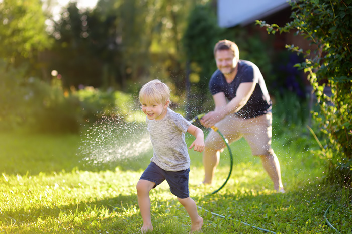 Funny little boy with his father playing with garden hose in sunny backyard. Preschooler child having fun with spray of water. Summer outdoors activity for kids.