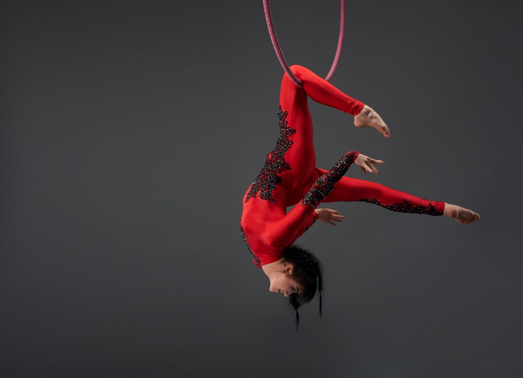 Woman in red balancing from hoop
