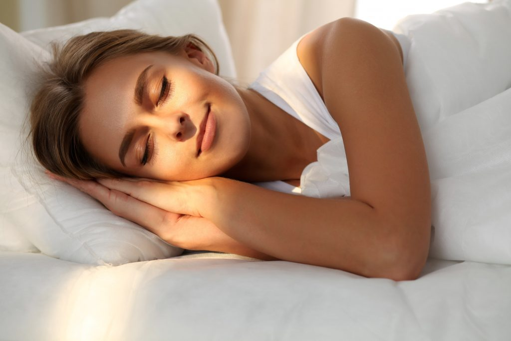 Woman sleeping with sunshine on her face