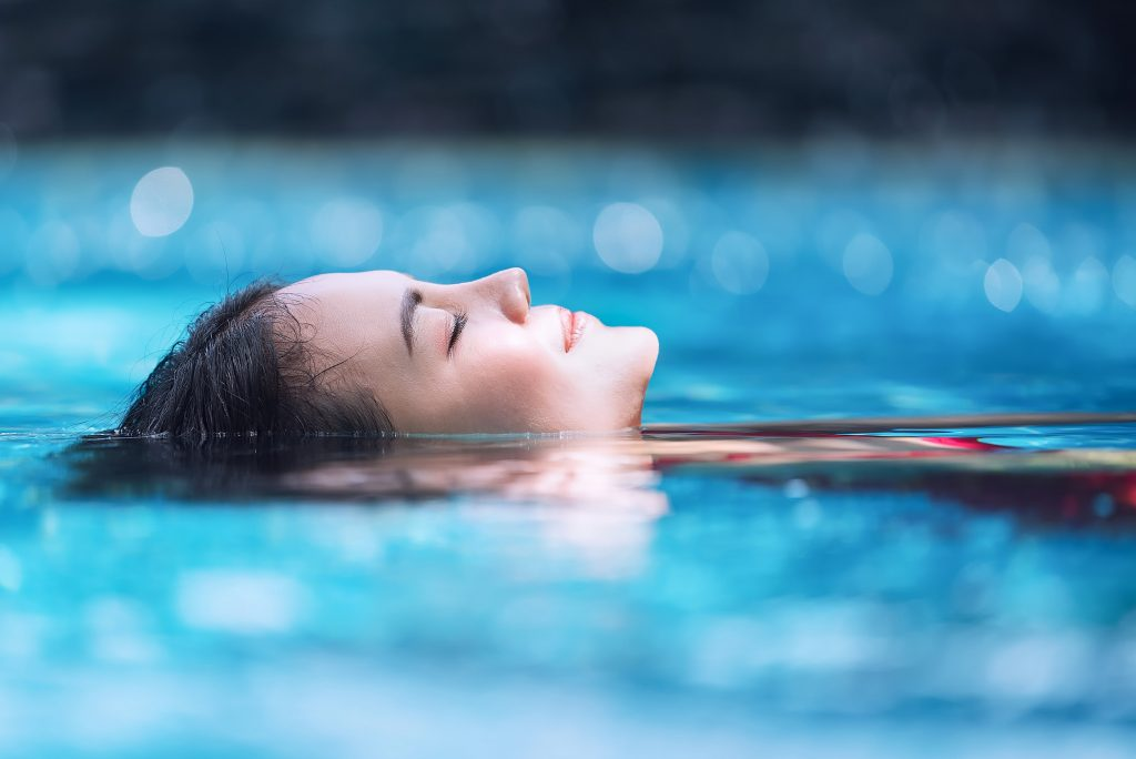 Smiling woman laying in pool of water