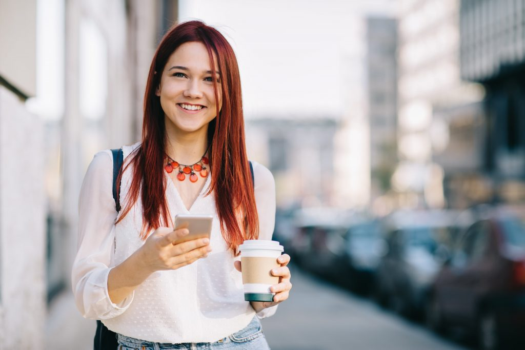 Girl with brown hair smiling and on her phone