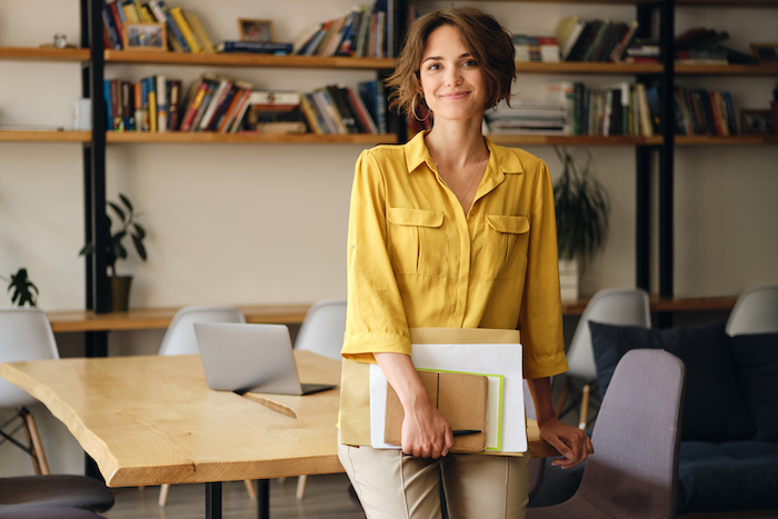 Young woman in yellow shirt leaning on desk with notepad and papers in hand while happily looking in camera in modern office