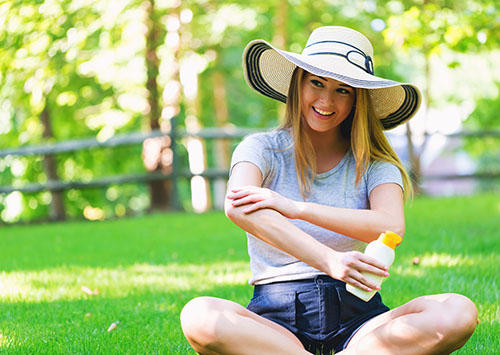 Young woman a bottle of suncream